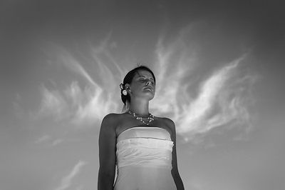 Photograph of a Bride with clouds behind here that look like Angel wings