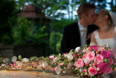 A Bouquet Of Wedding Flowers Is In The Foreground While The Bride And Groom Are Kissing In The Background