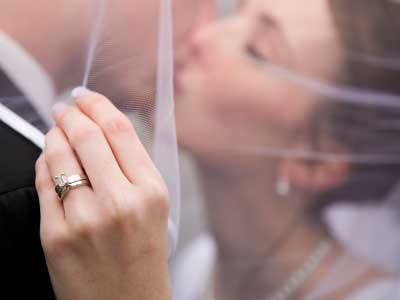 A Newly Married Couple Kissing Under The Bride's Veil With The Focus On Her Wedding Ring