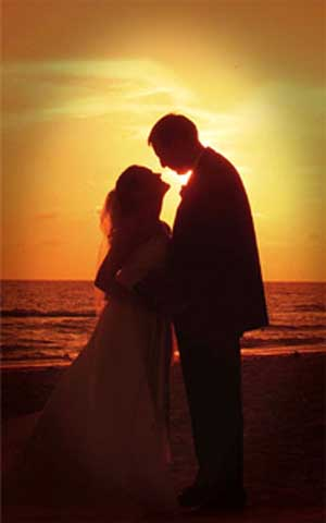 Silhouette of wedding couple kissing at sunset