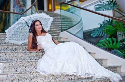 A Well Composed Photo Of A Newly-wed Sitting On Some Steps Posing With An Umbrella