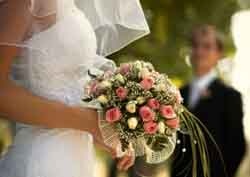 A Bride Holding Her Wedding Bouquet With The Groom Out Of Focus In The Background