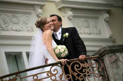 Picture Of The Groom Kissing His Beautiful Wife On A Balcony
