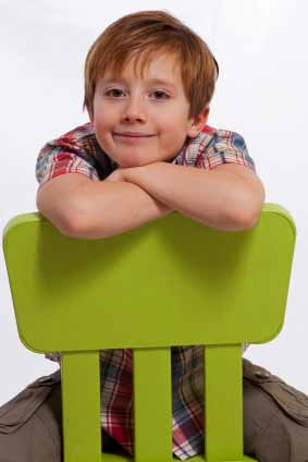 Young Boy Sitting On A Chair Backwards