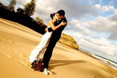 Picture Of Bride And Groom Kissing On The Beach With The Sun Shining On Them