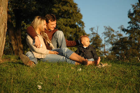 Family of three sitting on the grass in the park enjoying the Sun
