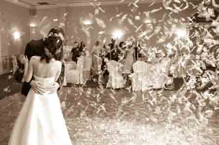 Bride and Groom having first dance showered in Confetti